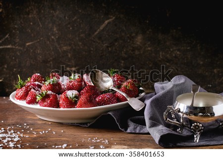 White plate with fresh ripe garden strawberries with sugar, sugar-bowl and spoons on wooden table. Dark rustic style. - stock photo