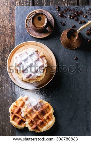 White plate with homemade belgian waffles with sugar powder, ceramic cup of coffee, old cezve and coffee beans. Over black slate as background. With copy space at right. Top view. - stock photo
