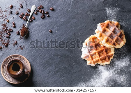 White plate with homemade belgian waffles with sugar powder, ceramic cup of coffee, teaspoon and coffee beans. Over black slate as background. With copy space at centre. Top view. - stock photo