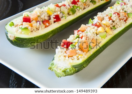 White plate with two zuchinnis stuffed with quinoa and vegetables - stock photo