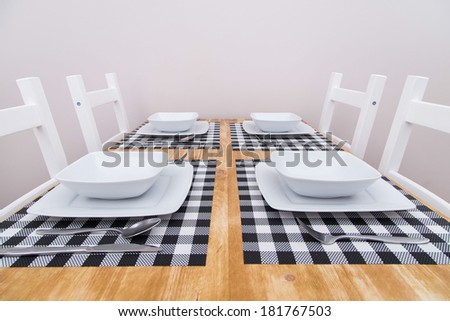 White plates and table service on a wooden table - stock photo