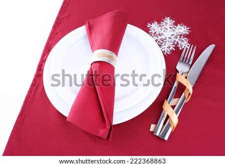 White plates, fork, knife and napkin on burgundy tablecloth isolated on white - stock photo