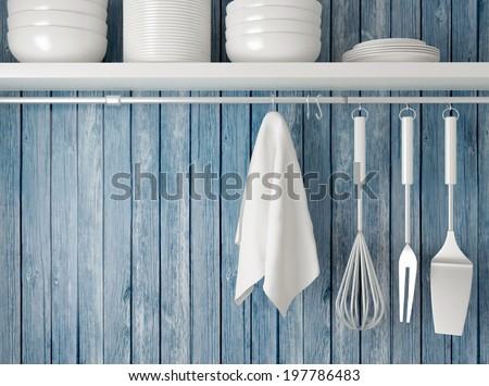 White plates on the shelf, kitchen cooking utensils. Steel spatulas, whisk and towel in front of rustic blue wooden wall.  - stock photo