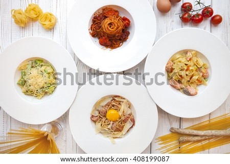 White plates with different Italian pastes decorated by ingredients on white wooden background. Top view - stock photo