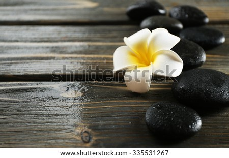 White plumeria flower with pebbles on wooden background - stock photo