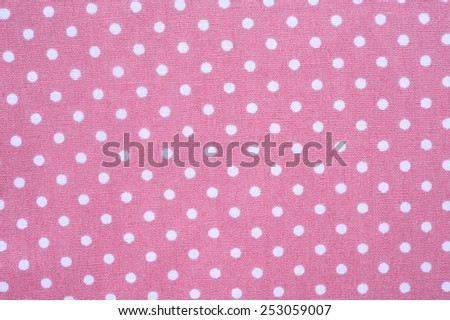 White polka dots on a tile pastel pink fabric background. - stock photo