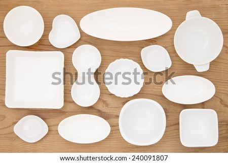 White porcelain dishes on a wooden background - stock photo