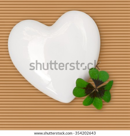 White porcelain heart and four leaf clover on brown corrugated paper; All the best for New Year; Good luck; Happy Valentine's Day - stock photo