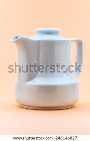 White porcelain milk jug on orange background. - stock photo