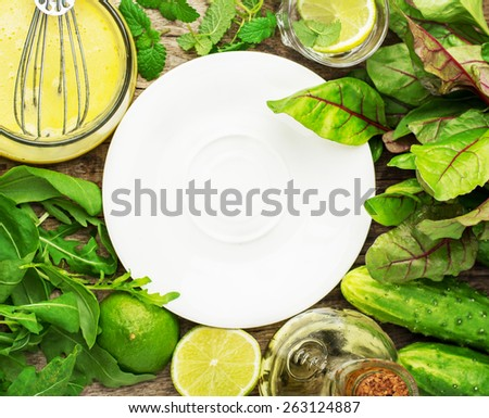 White porcelain plate on a wooden background surrounded razhlichnyh spring leafy vegetables, cucumbers and dressed with oil-based, lemon juice and egg yolk. Selective focus. Space for text. - stock photo