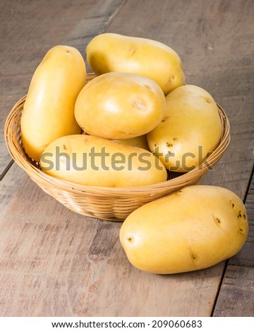White potatoes in a wicker bowl on a wooden table - stock photo