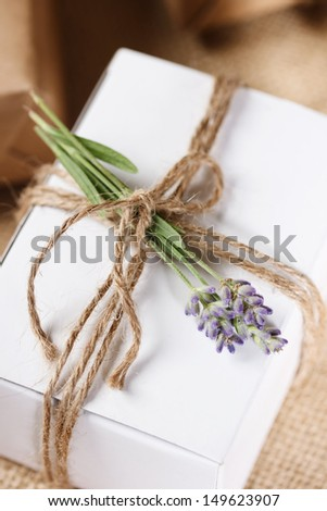 White Present box with rustic twine and sprig of lavender  - stock photo