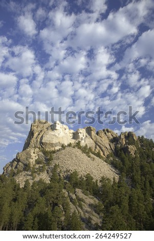 White puffy clouds behind Presidents George Washington, Thomas Jefferson, Teddy Roosevelt and Abraham Lincoln at Mount Rushmore National Memorial, South Dakota - stock photo
