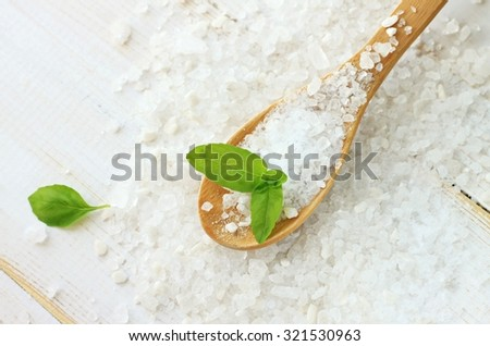 White pure sea salt granulated wooden spoon, fresh green basil herb, white empty background, culinary and spa health benefits - stock photo
