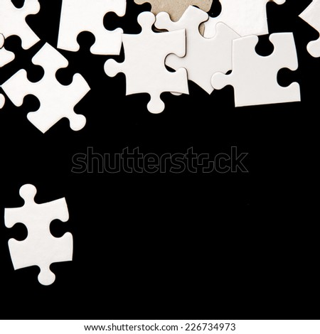 White puzzle on a black background - stock photo