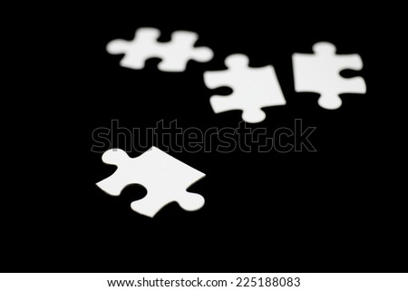 White puzzle on black background - stock photo