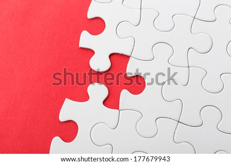 White puzzle on red background - stock photo