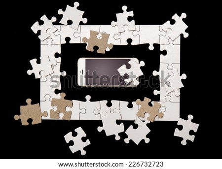 White puzzle with mobile phone on a black background - stock photo