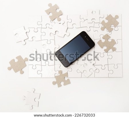 White puzzle with mobile phone on the table - stock photo