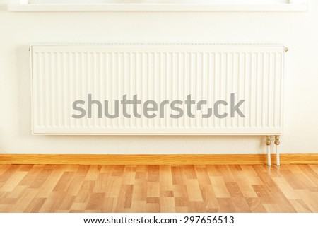 White radiator in the apartment framed with floor - stock photo
