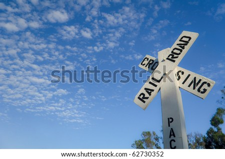 White railroad crossing sign under bright blue sky - stock photo