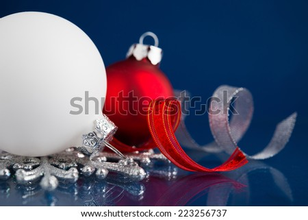 White, red and silver christmas ornaments on dark blue xmas background with space for text - stock photo