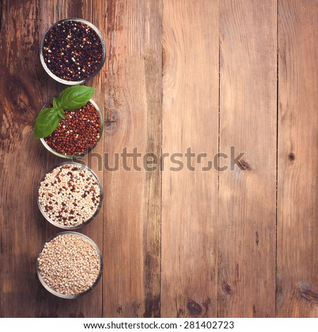White, red, black and mixed raw quinoa, South American grain, in glass bowls on old rustic woodenbackground. Top view. Background with copy space. Toned. - stock photo
