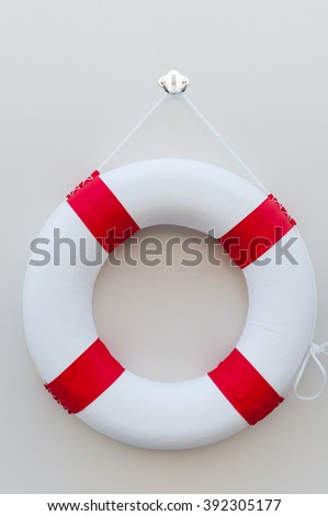 White red Lifebuoy with a board on white wall - stock photo