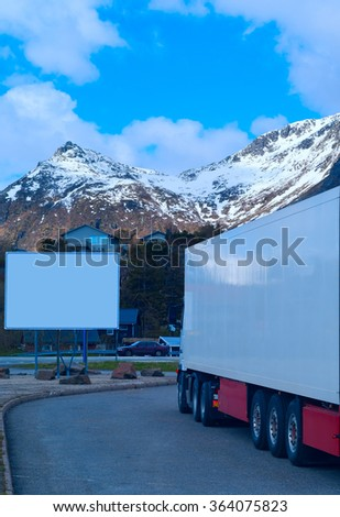 White refrigerated truck on background of the mountains and big white billboard - stock photo