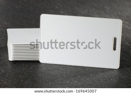 White RFID cards stacked on grey countertop - stock photo