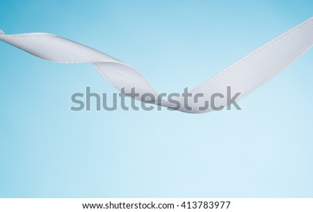 White ribbon isolated on a blue, pastel background. Product photograph taken in the studio on seamless paper background. - stock photo