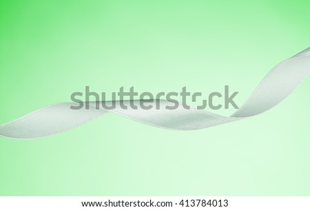 White ribbon isolated on a green, pastel background. Product photograph taken in the studio on seamless paper background. - stock photo
