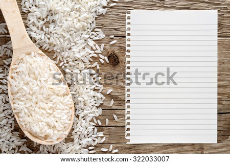 White rice and paper for recipe on wooden background - stock photo