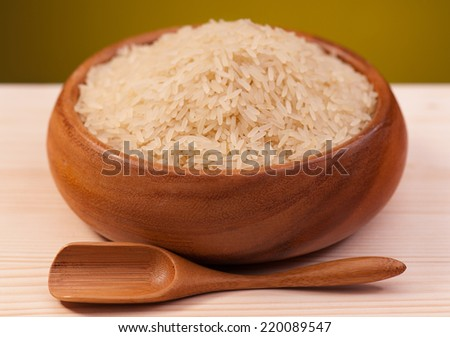 White rice in a bamboo bowl on a wooden surface over dark yellow background - stock photo