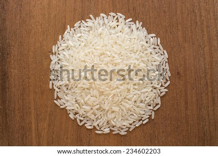 white rice on wood background - stock photo