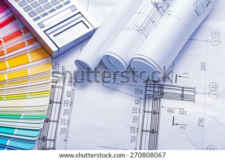 white rolled blueprints calculator and color palette construction concept  - stock photo