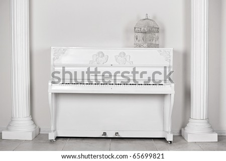 White room with columns and the piano about a wall - stock photo