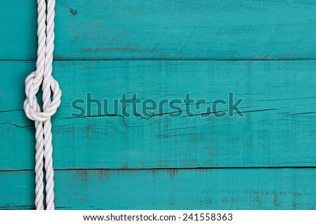 White rope with knot on blank  antique teal blue rustic wooden background - stock photo