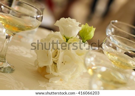 white roses and glasses with champagne on the table - stock photo