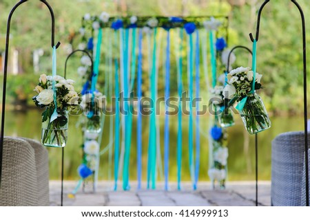 White roses and other flowers in two glass jar hung in wedding party. White roses, chrysanthemum in vase  with water. Wedding arch, decorated with colored ribbons on river bank. Wedding decorations. - stock photo