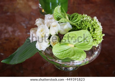 White roses and tropical leafs in a vase - stock photo