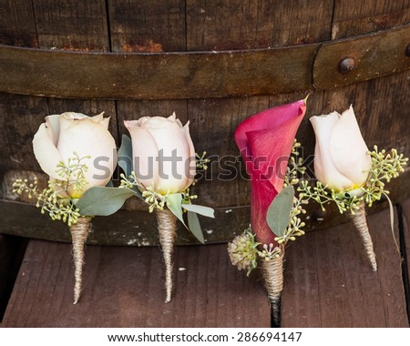 white roses groomsmen boutonniere and pink grooms lily wooden background - stock photo