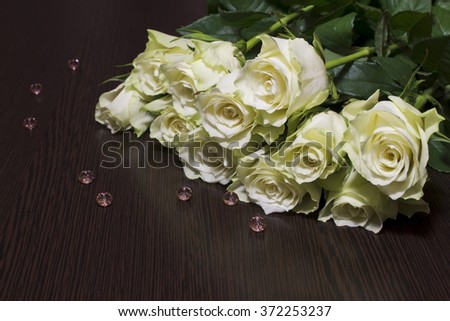 White roses on brown table. - stock photo
