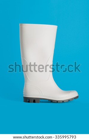 white rubber boot isolated on blue background - stock photo