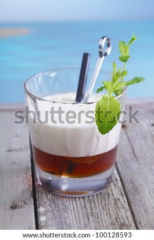 White Russian Coffee Cocktail with ice cubes and cream topping standing in a lounge at the beach, for alcoholic Drink Concepts. Visit my portfolio for more inspirations. - stock photo