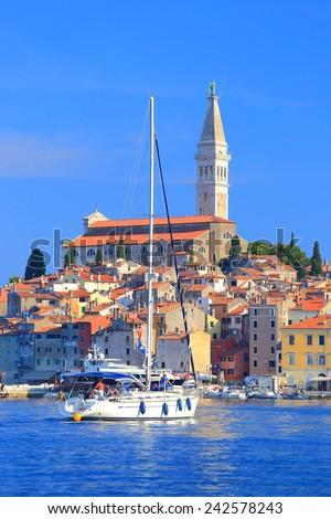 White sail boat approaches the harbor of old town near the Adriatic sea, Rovinj, Croatia - stock photo