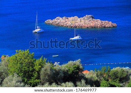 White sail boats anchored on the blue sea - stock photo