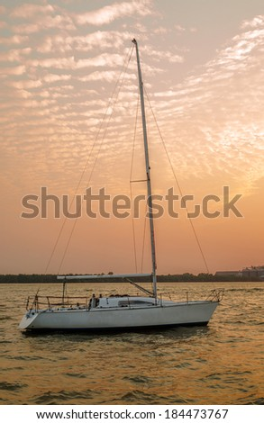 White sailboat and golden sky in twilight time - stock photo