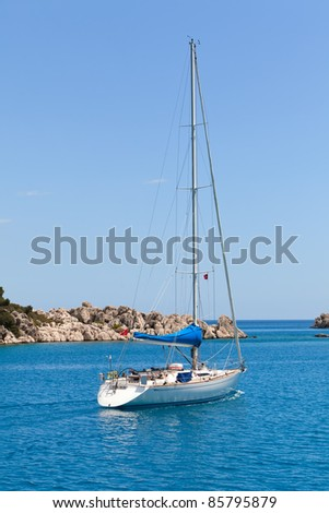 White sailboat in turkish bay on blue sea - stock photo