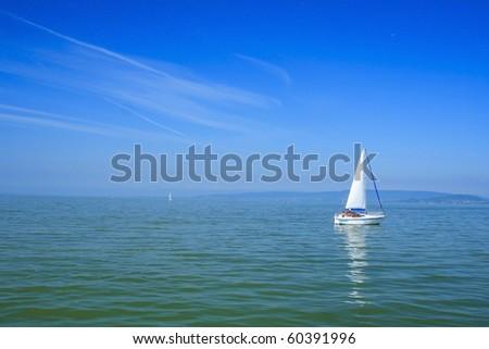 White sailboat with blue background in lake Balaton - stock photo